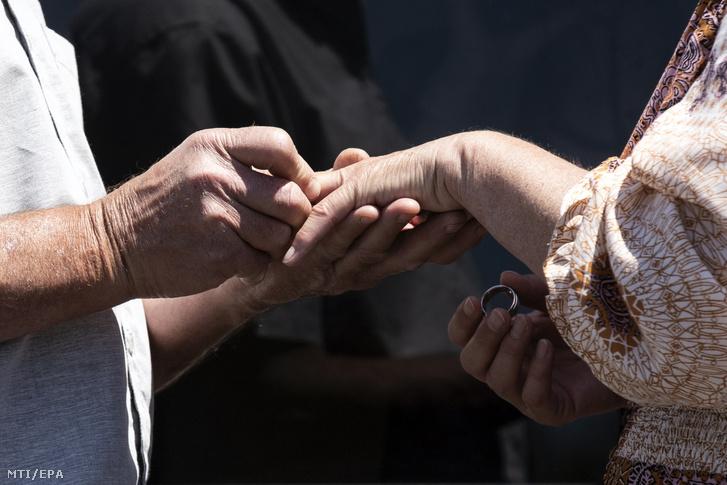 Gyűrűt húz menyasszonya ujjára egy férfi a kaliforniai Anaheimben 2020. április 23-án