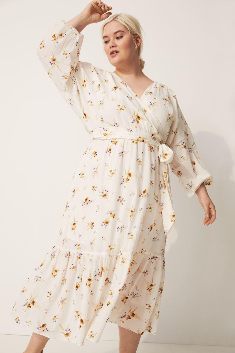 A H&M romantikus, virágos ruhája átlapolt felsőrészének és kötőjének köszönheti alakformáló hatását. 11 995 forintért vásárolhatod meg.