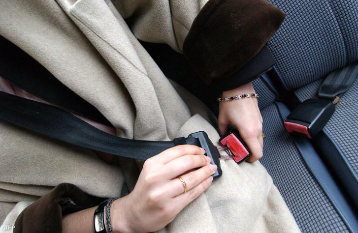 Egy nő bekapcsolja hárompontos biztonsági övét egy autóban