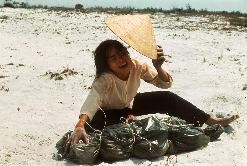 Tömegsírból előkerült halott férjét siratja egy vietnami nő.