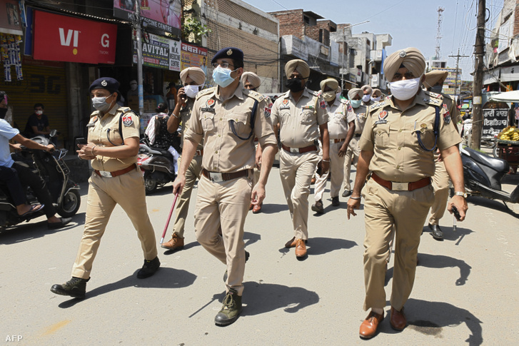 Indiai rendőrök járőröznek egy, a járványügyi korlátozások által érintett faluban május 14-én