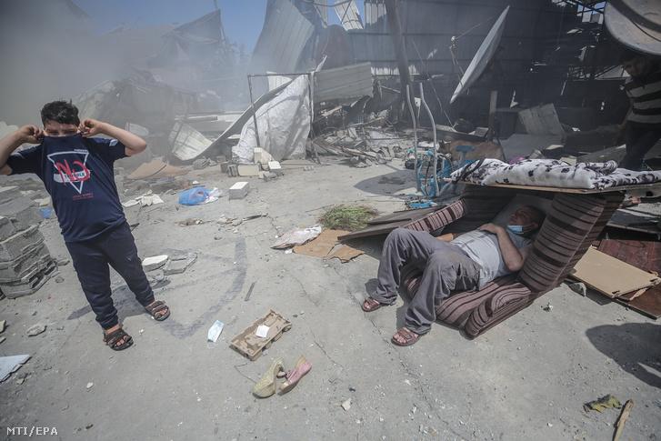 Palesztinok egy izraeli légicsapásban megrongálódott lakóház romjai között Gázában