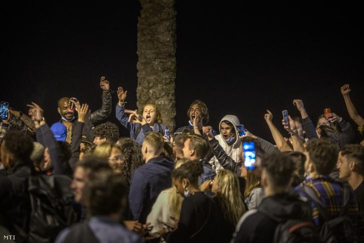 Tömegek ünnepelnek Barcelona tengerparti strandján 2021. május 9-én hajnalban, miután éjfékor véget ért a 2020 októbere óta érvényben lévő szükségállapot és a kijárási tilalom. Ettől a naptól kezdve újra szabadon lehet utazni a tartományok között. Az egyes régiók kormányainak mostantól bíróságon kell érvényt szerezniük a járványügyi korlátozások jogosságának.