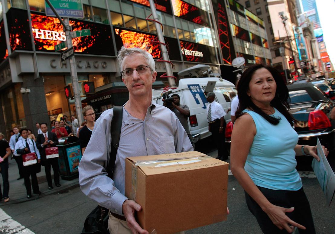 A Lehman Brothers Holdings Inc. munkatársa egy dobozt visz ki a vállalat székházából (háttérben), miután a cég csődöt jelentett be 2008. szeptember 15-én, New York Cityben