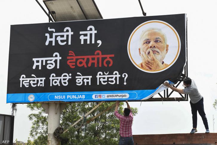 Egyetemisták egy Narendra Modi miniszterelnök járványkezelését kifogásoló plakátot helyeznek elAmritszár városában