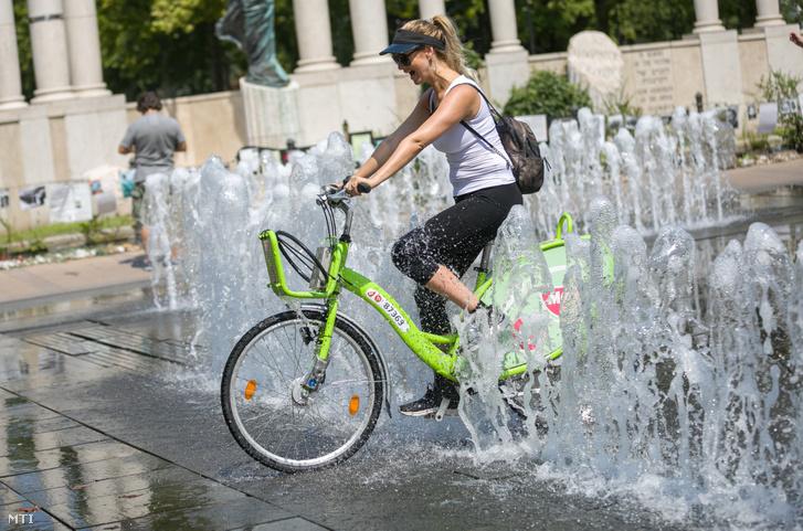 Kerékpározó nő hűsíti magát egy szökőkút vizében a kánikulában a budapesti Szabadság téren 2020. augusztus 9-én