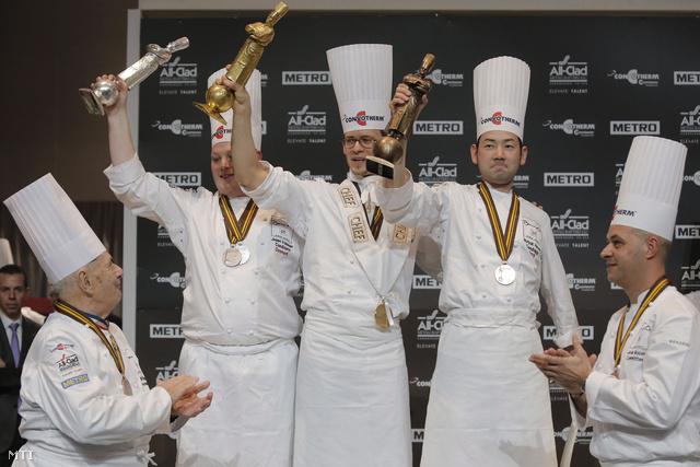 A versenyt alapító Paul Bocuse francia mesterszakács (b) és a fia Jerome Bocuse megtapsolja az első Thibaut Ruggeri francia séfet (k) a második dán Jeppe Foldagert (b2) és a harmadik japán Hamada Norijukit