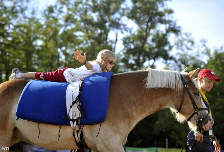 Egy látássérült kislány gyógypedagógiai lovastorna-bemutatót tart a Nemzetközi Gyermekmentő Szolgálat és a Magyar Lovasterápia Szövetség lovasterápiás versenyén a fóti Lovasterápiás Központban 2012. szeptember 21-én