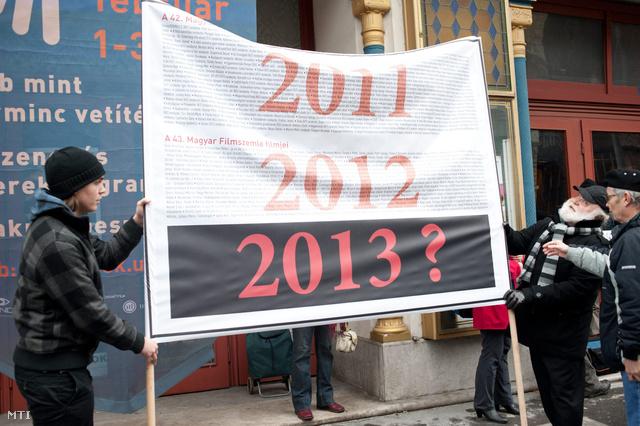 Böjte József (j) újságíró a flashmob szervezője egy transzparenst nyit ki az évente rendszeresen megrendezésre kerülő Magyar Filmszemle szokásos idejében a Magyar Filmművész Szövetség rendkívüli nyilvános közgyűlését megelőző flashmobon