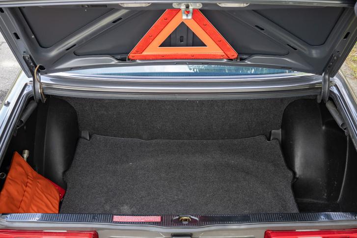 Szépen kárpitozott csomagtér, ha nem lenne ilyen magas a perem, könnyű lenne megpakolni. Az utód W124 már mélyre nyúló fedelet kapott