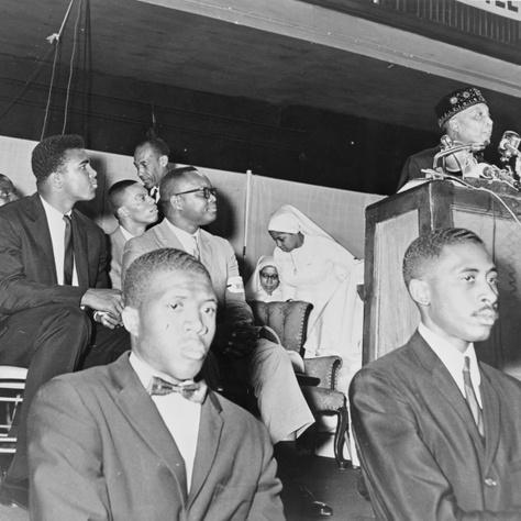Elijah Muhammad szektavezér prédikáció közben, a hallgatóság tagjai közül Ali (balra) is figyelmesen hallgatja