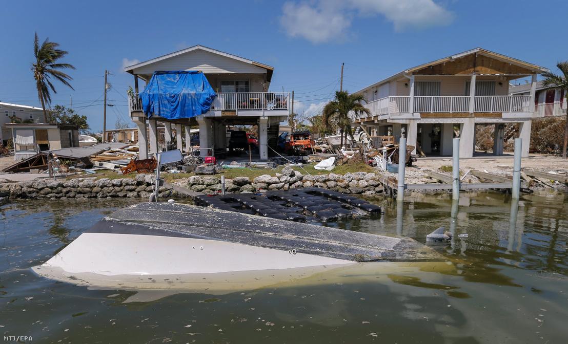 Felborult csónak megrongálódott tengerparti házak előtt a floridai Marathonban 2017. szeptember 12-én az Irma hurrikán elvonulása után