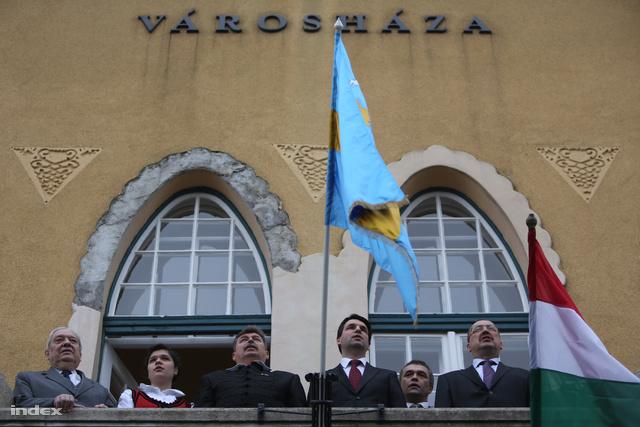 A városháza teraszán a meghívott díszvendégek és a Szabolcs Attila polgármester éneklik a székely himnuszt a zászlótűzésen. Pozsgay Imre Budafokon tűzhetett székely zászlót a városháza épületére, és a Tisztességes Választásért Alapítvány nevében két másik önkormányzatnak is adott egyet-egyet.