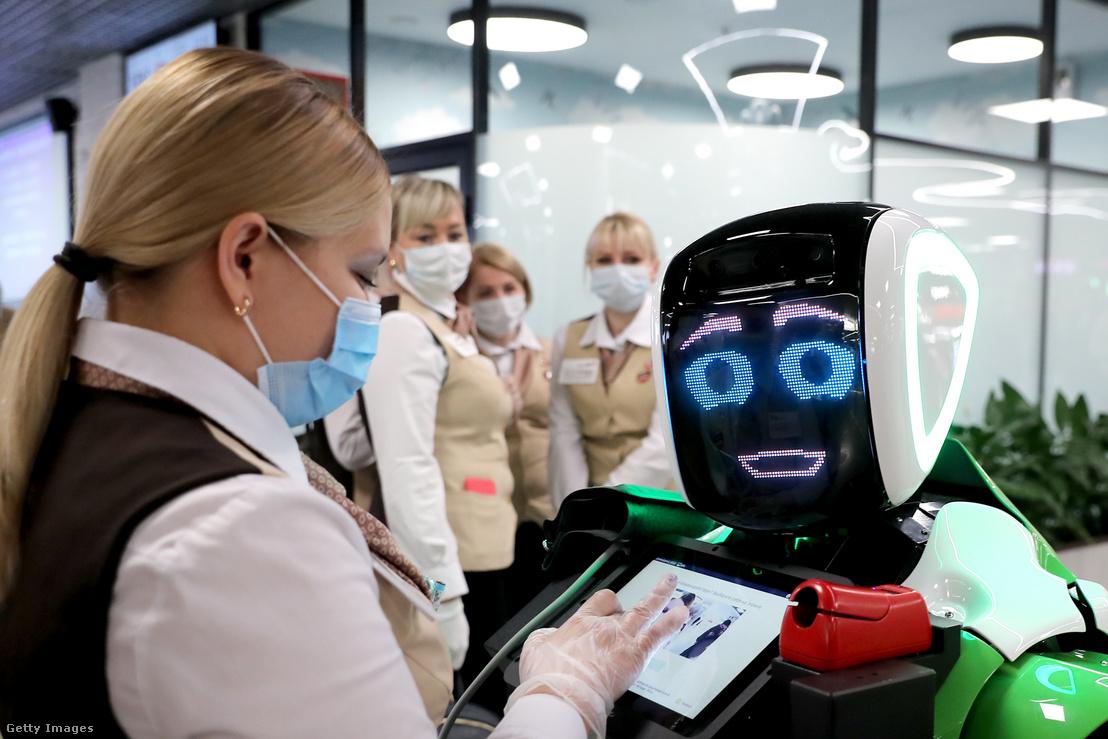 Egy személyzet egyik tagja robotasszisztenst működtet egy bevásárlóközpontban 2021. január 29-én Moszkvában