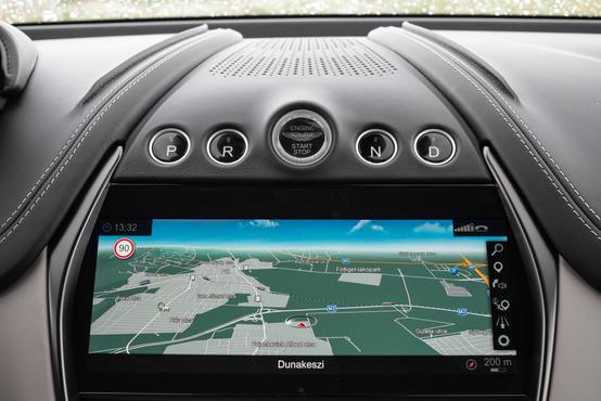 A navigációs kijelző feletti nagy gomb az indító, a négy kicsi az automataváltó kapcsolói. Viszonylag messze a sofőrtől, de legalább gyorsan reagál rájuk a szerkezet