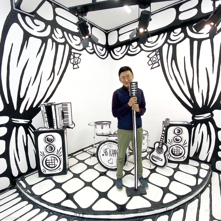 A kélpen az ismert tervező, Anfisa Toshina látható abban a fekete-fehér színekben pompázó kávézóban, melyet ő álmodott meg