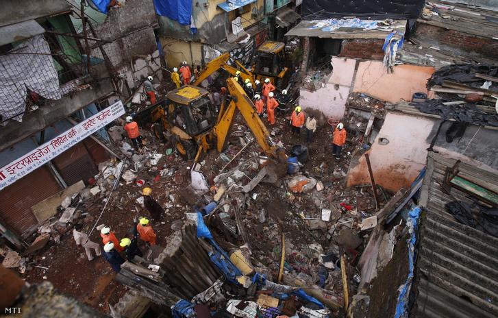 Mentőalakulatok tagjai kutatnak túlélők után egy összedőlt háromemeletes épület romjai között Mumbaiban 2021. június 10-én