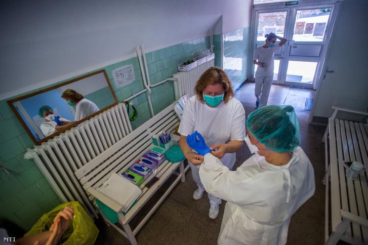 Ápoló segít védőfelszerelésbe beöltözni egy orvosnak 2020. május 14-én