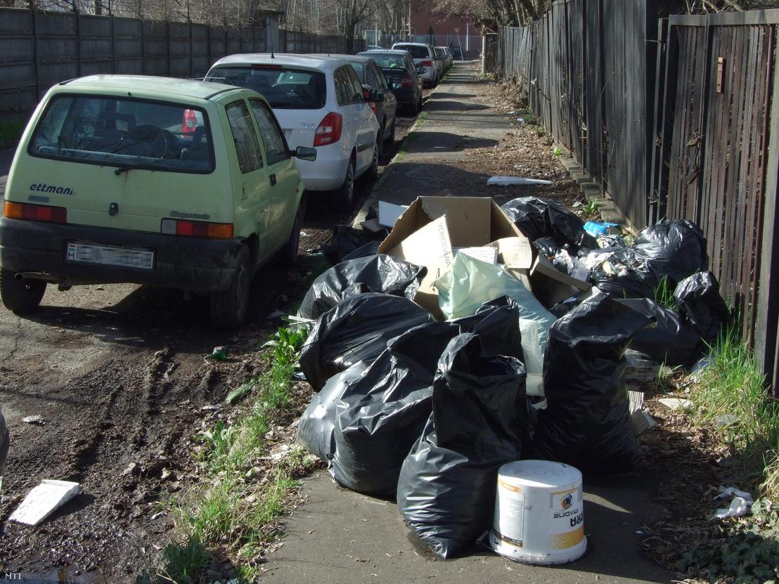 Engedély nélkül lerakott építési hulladékot tartalmazó műanyag zsákok a főváros XI. kerületének egyik kis forgalmú zsákutcájának járdáján 2016. február 22-én