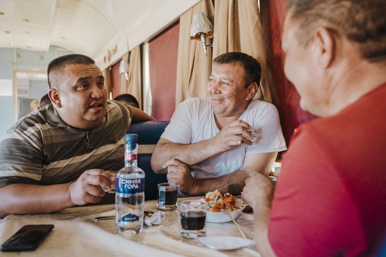 A büfékocsikban mindig pezsgő a hangulat. A vagonok nevetéssel, a borscht leves illatával telnek meg. A pincérnő sorra viszi az asztalokhoz az üveg vodkákat a többségében férfiakból álló vendégeknek. 2019. október 4.