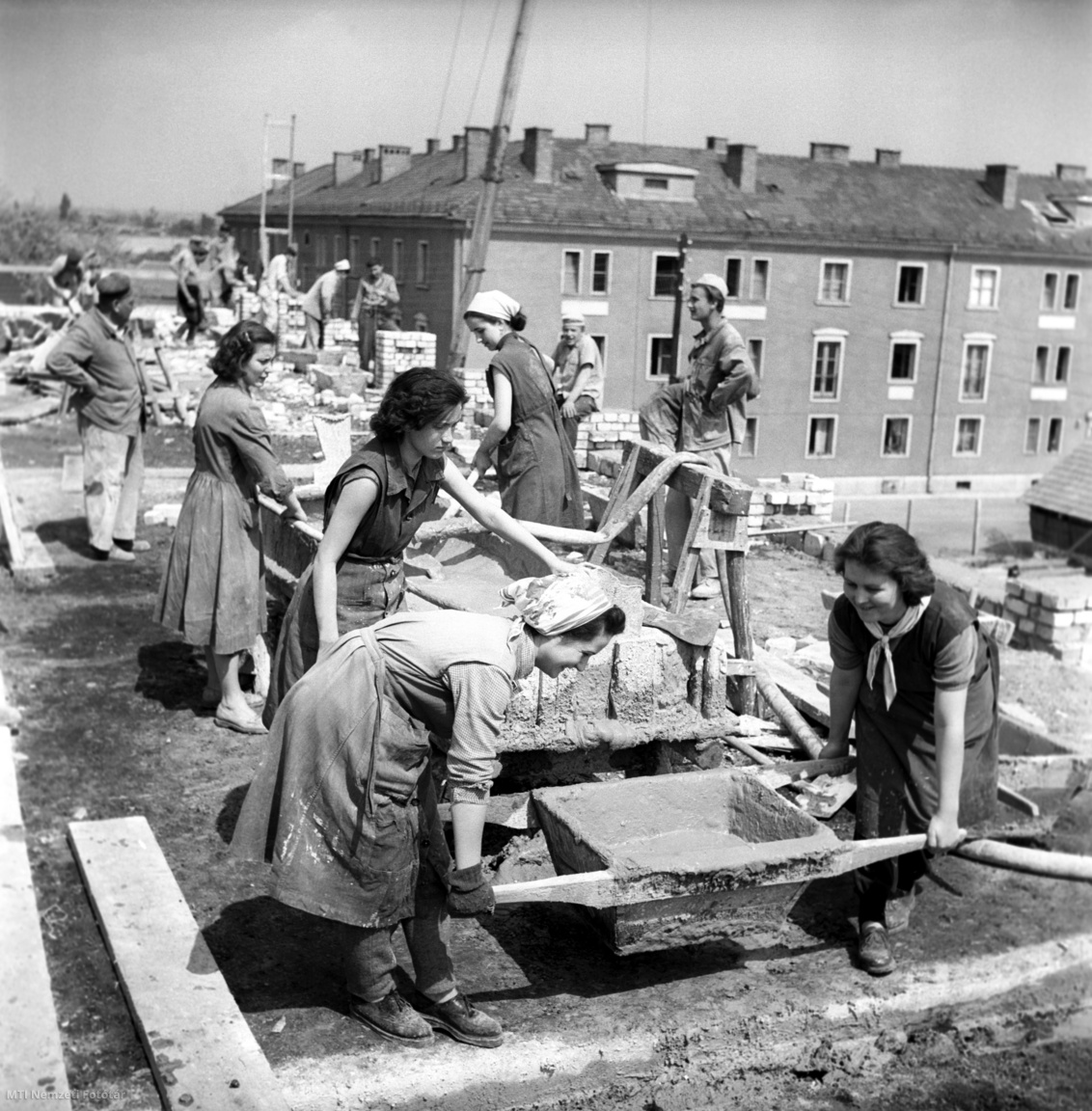 1959. május 5. A Hazai Fésűsfonó KISZ (Kommunista Ifjúsági Szövetség) tagjai dolgoznak fizetett szabadságukon a pesterzsébeti Csarnok téren épülő iskolánál. A munkát a Világifjúsági Találkozó (VIT) tiszteletére vállalták