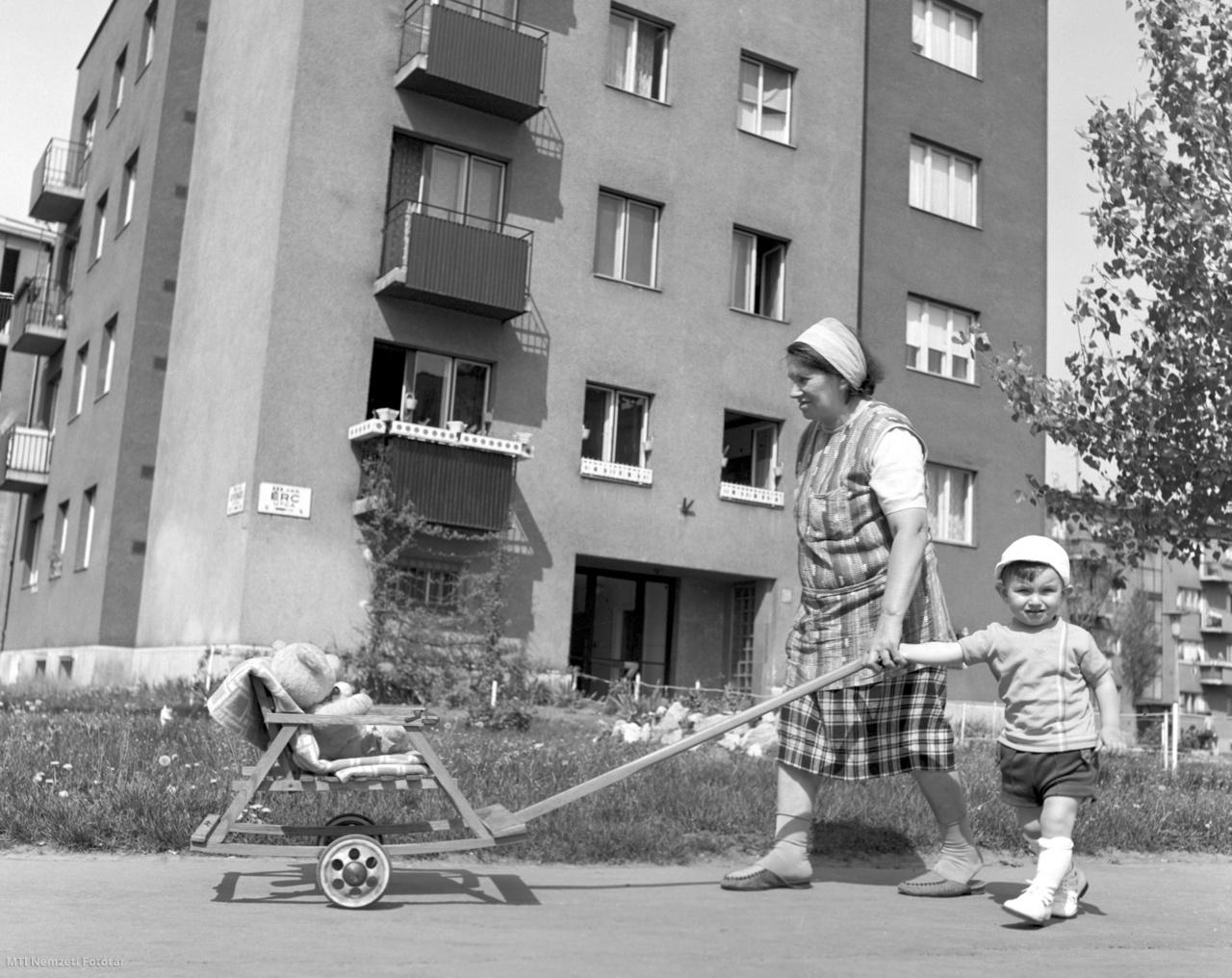 A nagypapa által épített kis kocsit toló nő sétál unokájával, Füredy Jánossal az  óbudai Érc utcai kísérleti lakótelepen 1969. május 6-án. Óbuda nagy változások előtt állt. Az 1968-ban lebontott régi földszintes házak helyén megkezdték a házgyári lakóházak építését
