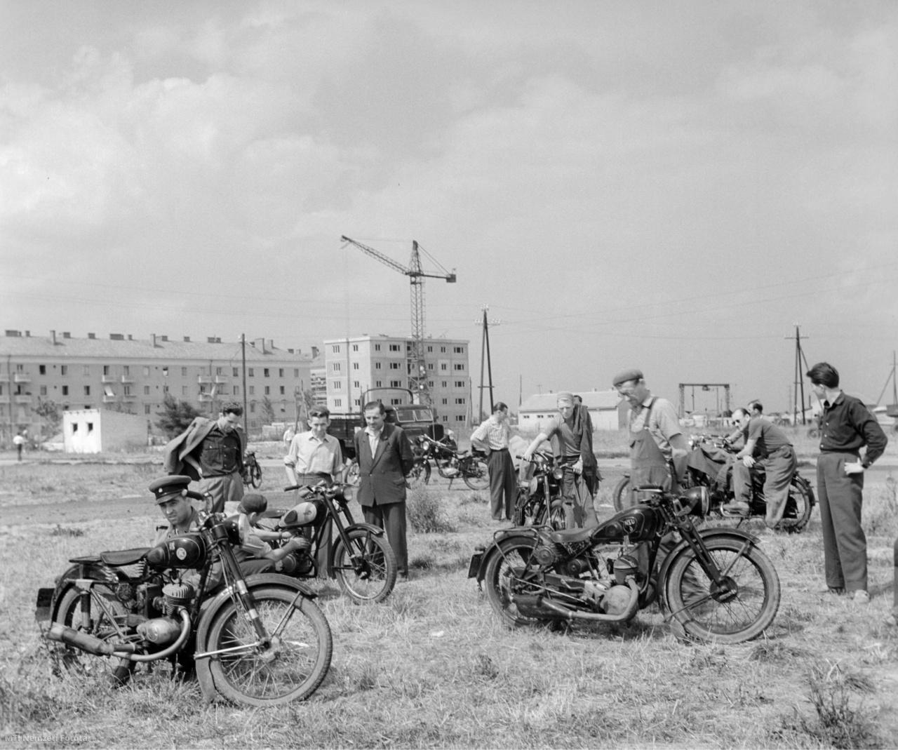 Motorkerékpárosok járműveikről beszélgetnek törzshelyükön a  Dózsa György út és a Sztálin út sarkán Sztálinvárosban, 1959. július 7-én