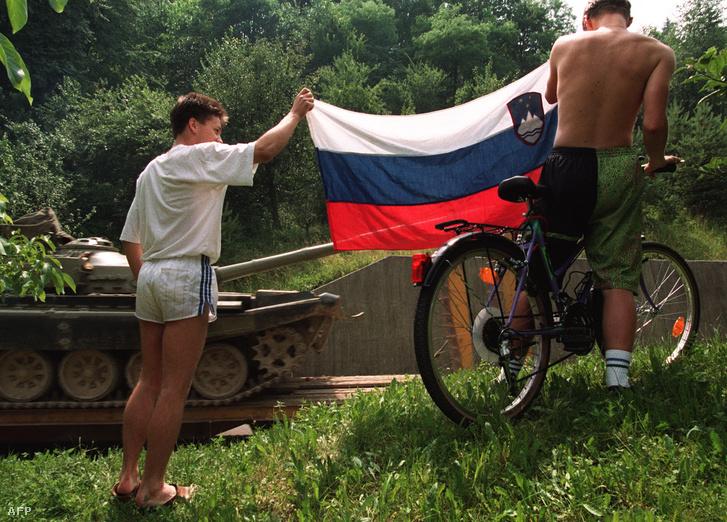 Két szlovén fiatal emeli elszakadt köztársaságának zászlaját, amikor a jugoszláv hadsereg egyik T-55-ös harckocsiját szállítják el mellettük1991. július 05-én, Ljubljanában