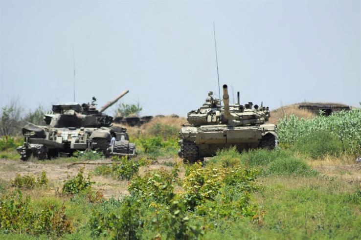Egy azeri tank álldogál büszkén egy kilőtt örmény páncélos mellett.