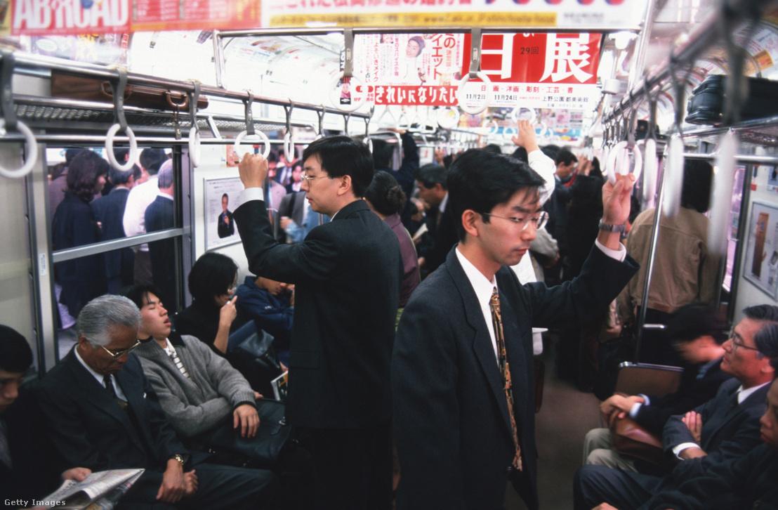 Japánok utaznak a metrón Tokióban