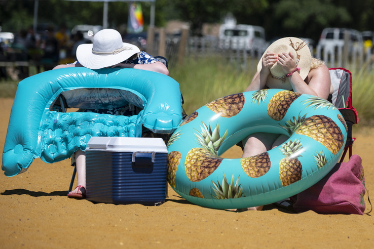 Two women blow up floaty tubes as they try to escape the heat at Sandy Point State Park in Annapolis Maryland on June 29 2021.