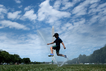 Children play in sprinklers on the National Mall as the DC area experiences a heatwave  on June 30 2021 in Washington DC