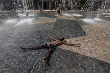 Egy férfi a városháza előtti szökőkutak vízében hűti le magát a hőségben a kanadai Edmontonban 2021. június 30-án