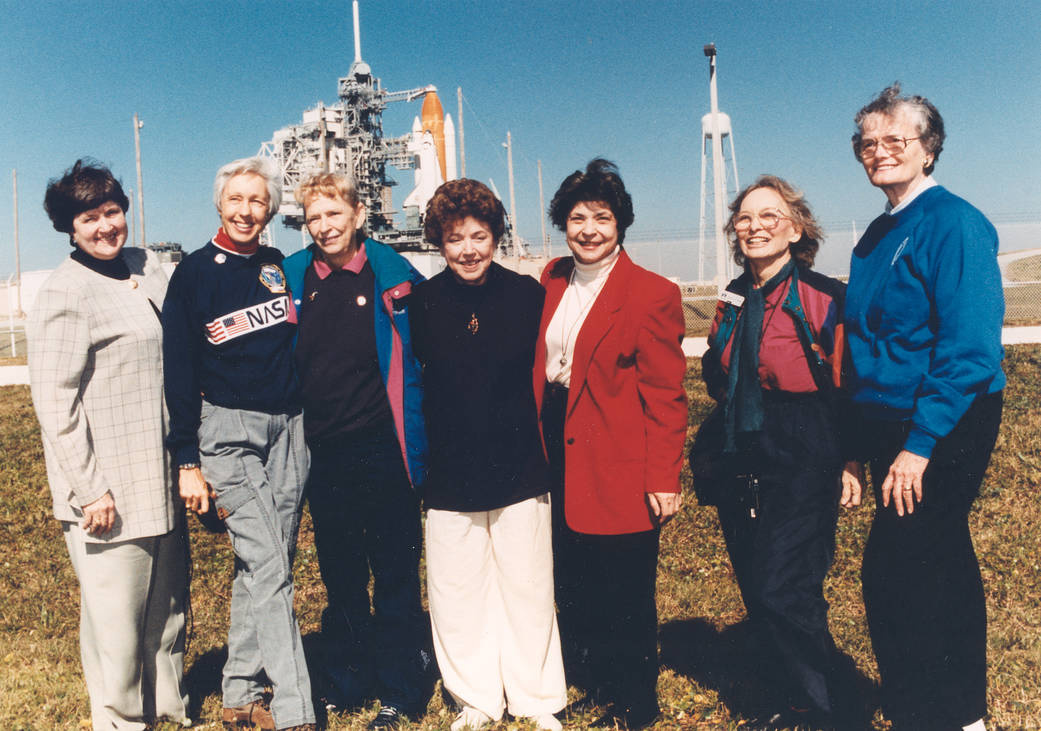 Heten a FLAT-program résztvevői közül 1995-ben, háttérben a kilövésre készülő Discovery űrsiklóval. A képen balról jobbra Gene Nora Jessen, Wally Funk, Jerrie Cobb, Jerri Truhill, Sarah Rutley, Myrtle Cagle és Bernice Steadman látható