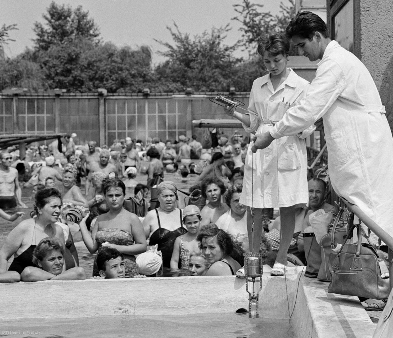 A Budapest Fővárosi Közegészségügyi és Járványügyi Állomásának egészségügyi ellenőrei ellenőrzik a Dagály utcai Szabadság Strandfürdő termálvizes medencéjében a vízminőséget 1964. július 23-án. A kánikulai melegben tízezrek keresik fel a budapesti strandokat ezért fokozott gondossággal ügyelnek a területek és medencék vízének tisztaságára.