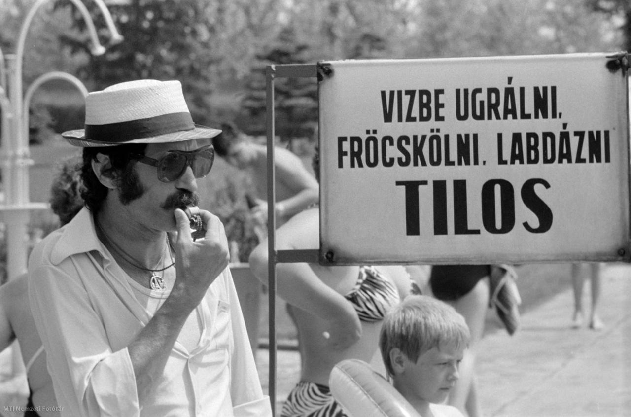 Úszómester sípol a hatvani strand medencéjénél a Vízbe ugrálni fröcskölni labdázni tilos feliratú tiltó tábla mellett 1985. május 25-én, Hatvanban.