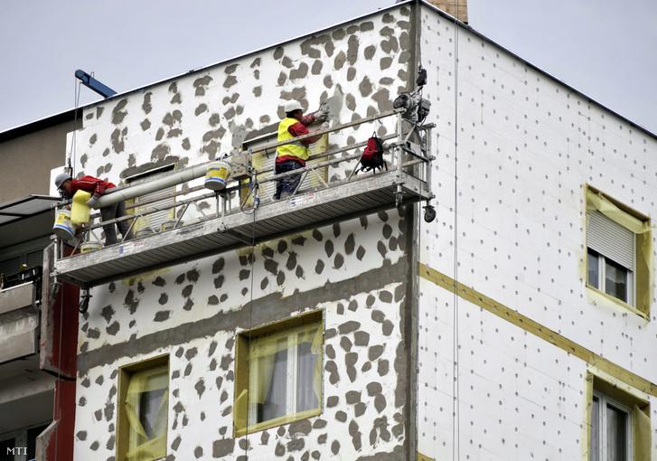 A külső szigetelés rögzítését és vakolását végzik munkások egy épületen