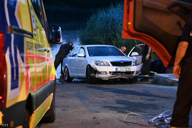 Tűzoltók vontatnak ki egy személygépkocsit a Dunából Csepelen a Hollandi útnál a kompkikötő közelében 2021. július 9-én