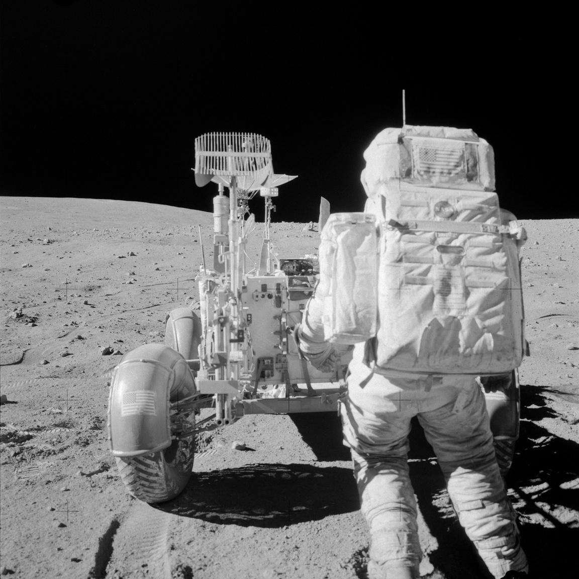 John W. Young éppen eszközöket pakol a holdjáró kéziszerszámtartójába az Apollo-16 misszió második űrsétáján. Eredetileg az Apollo-16-on akarták volna először használni a holdjárót, de a program újratervezése végett az Apollo-15 asztronautái autóztak először az űrben. Az Apollo-16 holdjárójával gondok voltak, az összehajtogatott kerekek nem álltak automatikusan pozícióba és a hátsó kerekek kormányzása sem akart működni.