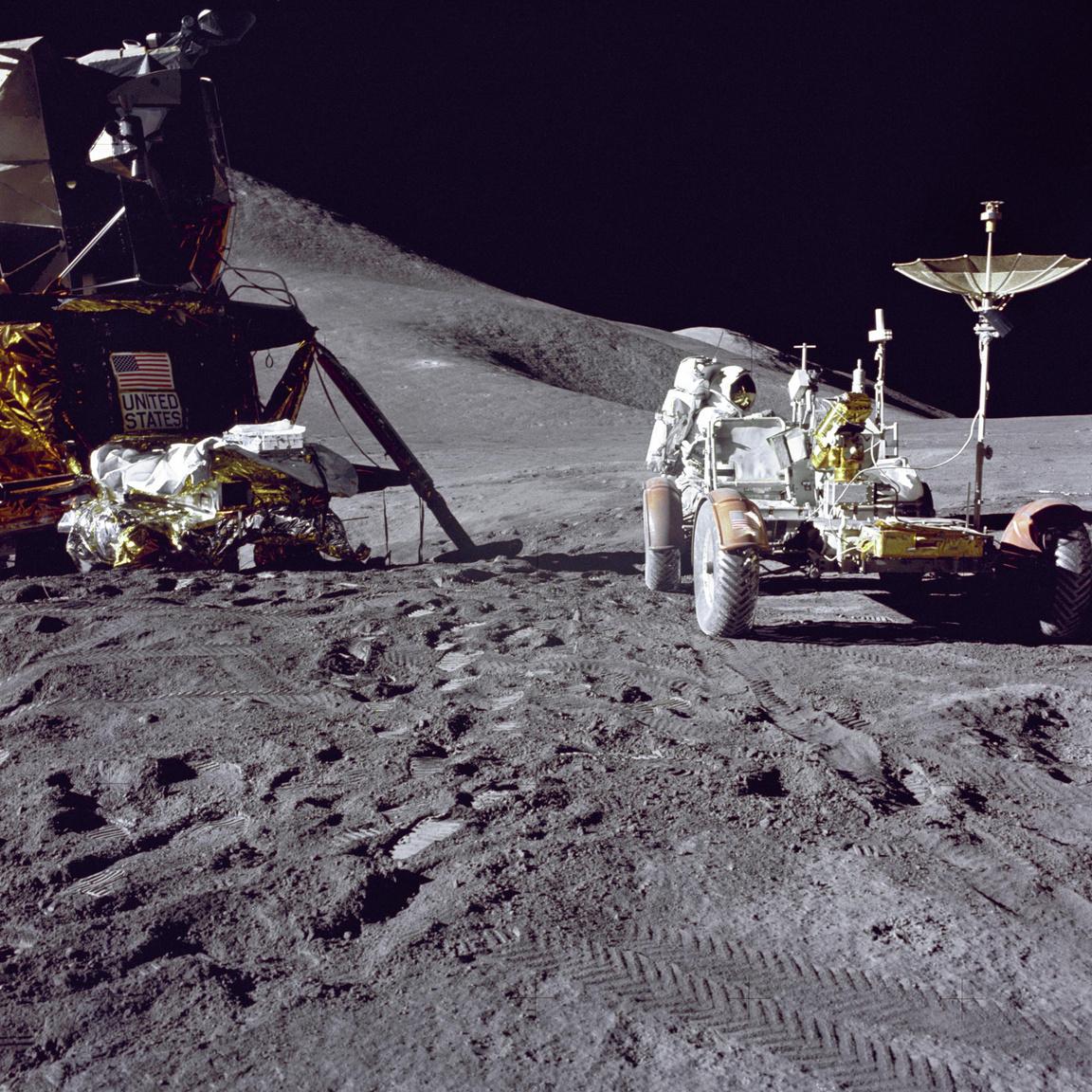"""A leszállóegység pilótája, Jim Irwin felkészíti a már összeállított holdjárót az Apollo-15 első holdsétájára. A holdjáró úgy lett kialakítva, hogy """"lapra hajtva"""" elférjen a holdkomp oldalában és rugós szerkezetének segítségével 20 perc alatt összeállíthassák az űrhajósok. A holdjáró széthajtogatta magát, még kerekeit is irányba állította, az űrhajósoknak csupán az üléstámlákat és a kormányoszlopot kellett helyükre tenni és a mérőeszközöket, felszerelést felpakolni."""