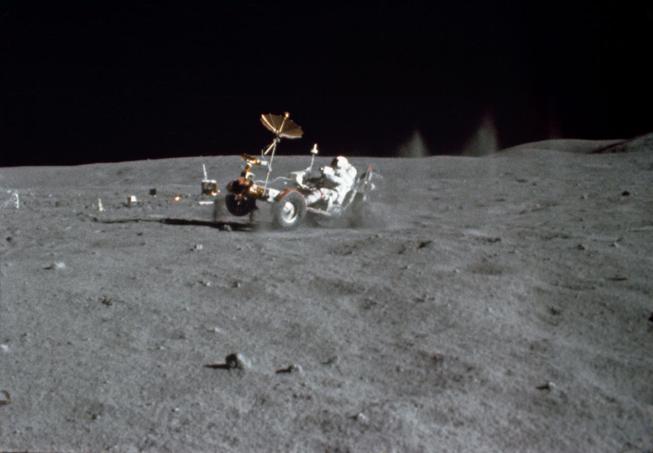 John Young meghajtja a holdjárót az Apollo-16 első holdsétáján, 1972. április 21-én. A fotót egy 16 milliméteres filmre rögzítő speciális Mauer kamera által felvett mozgóképből vágták ki, melyet Charles M. Duke Jr. tartott kezében. A kép érdekessége a felverődő por és kőzet látványa, illetve az, hogy a rover kerekei nem érik a talajt. Az Apollo-16 holdautója fel volt szerelve egyébként egy saját tévékamerával is, de ezt csak megállás után lehetett használni, mert mindig a Föld irányába kellett állnia az átjátszó antennának, hogy fogni tudják a Holdról érkező adást.