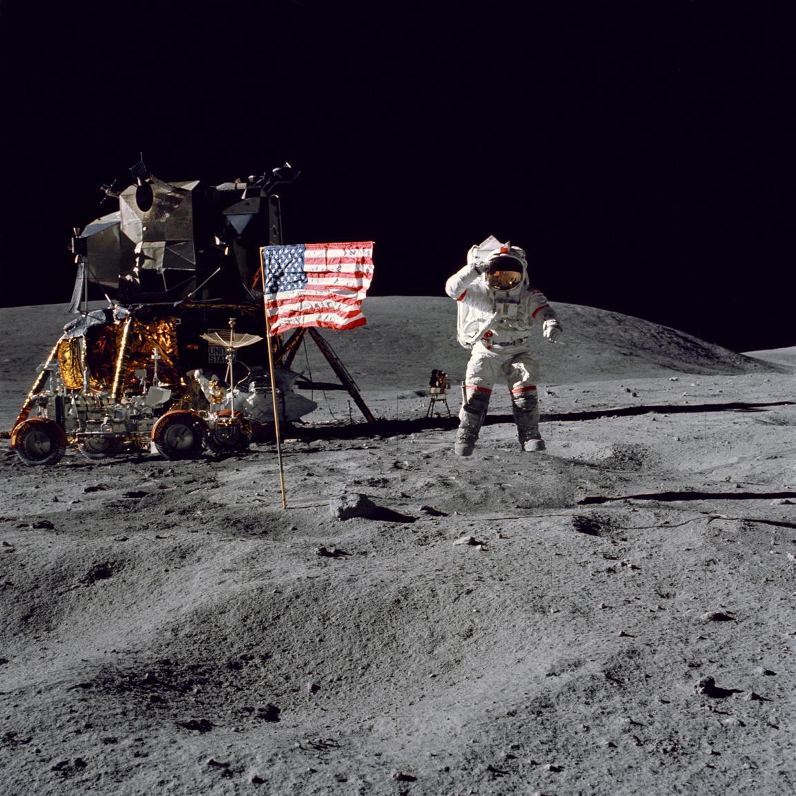 Bár a játékfilmekből azt hihetjük, hogy az űrhajósok első dolga volt a holdraszállás után felállítani az amerikai zászlót és felvételeket készíteni vele, ez nem igaz. Első lépésként a holdjárót kellett összeállítani, majd kipakolni a felszerelést és beállítani a mérőeszközöket. Az Amerikai Egyesült Államok zászlajának felállítása valójában az utolsó holdkomp körüli teendő volt. A fotó készültekor John W. Young parancsnok tréfásan felugrott, így lebegve tiszteleg az amerikai zászló előtt. Háttérben balra látható a holdautó, mögötte a holdkomp.