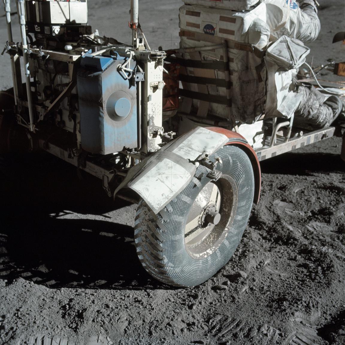 """Közeli fotó, ami a sárvédő ideiglenes javításáról készült a Holdon. A NASA először 1999-ben tette közzé a képet az interneten """"Holdpor és Ragasztószalag"""" címmel. A holdautót tartalék térképekkel, fogókkal és ragasztószalaggal kasztnizták. A 38 millió dollárból kifejlesztett járműveket a missziók után nem hozták vissza a Földre, a mai napig a Holdon vannak."""