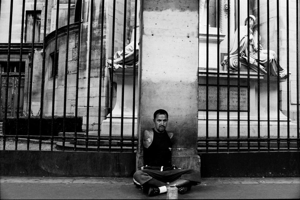 Egy kar nélküli roma férfi koldul Párizsban a Louvre mellett.