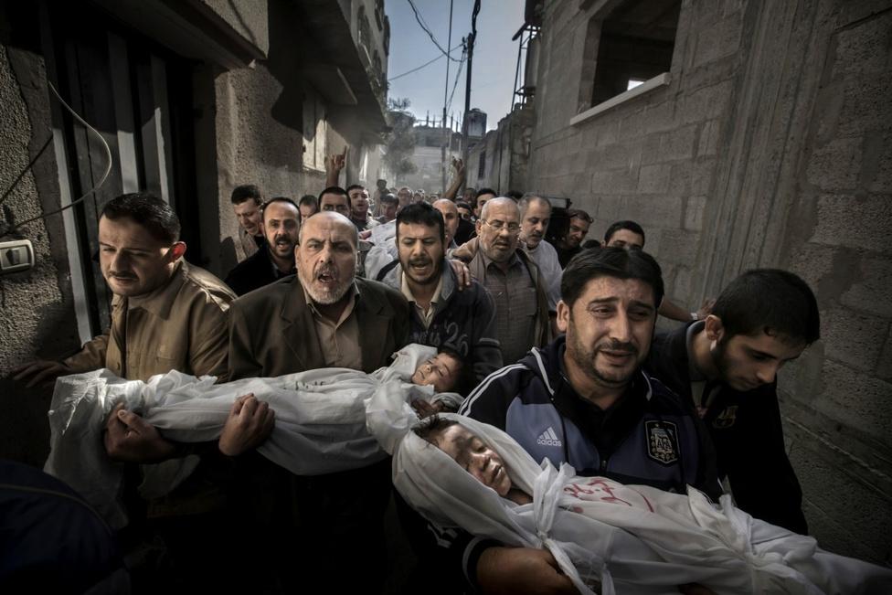A World Press Photo Nagydíja - Két halott palesztin gyereket tartanak kezükben rokonaik. A gyerekek a novemberi izraeli bombázás során vesztették életüket.