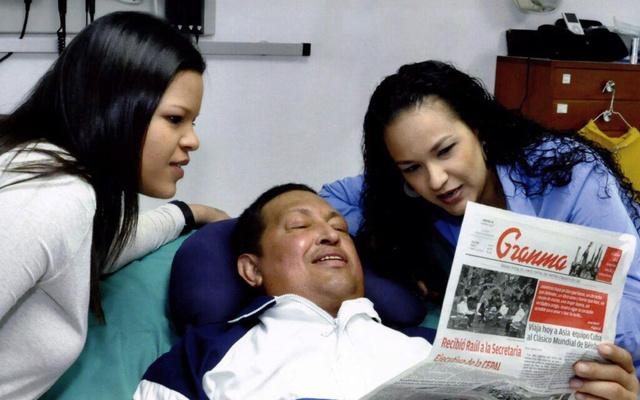 A Miraflores Elnöki Sajtóiroda által 2013. február 15-én közreadott képen Hugo Chávez venezuelai elnök a Granma című kubai napilapot olvassa lányai, Maria Gabriela (b) és Rosa Virginia társaságában Havannában 2013. február 14-én.