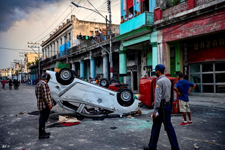 Rendőri járőrkocsikat döntöttek fel az utcán a kormányellenes tüntetés során Havannában, 2021. július 11-én