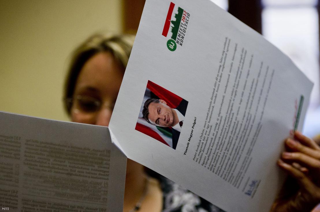 Egy újságíró olvassa a tizenhat elsősorban munkahelyteremtéssel kapcsolatos kérdést tartalmazó új nemzeti konzultáció kérdőívét a Miniszterelnökségen tartott sajtótájékoztatón 2012. május 30-án