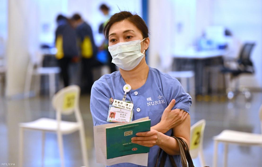 Koronavírus elleni vakcinával beoltott egészségügyi dolgozó távozik az oltópontról Hongkongban 2021. február 23-án