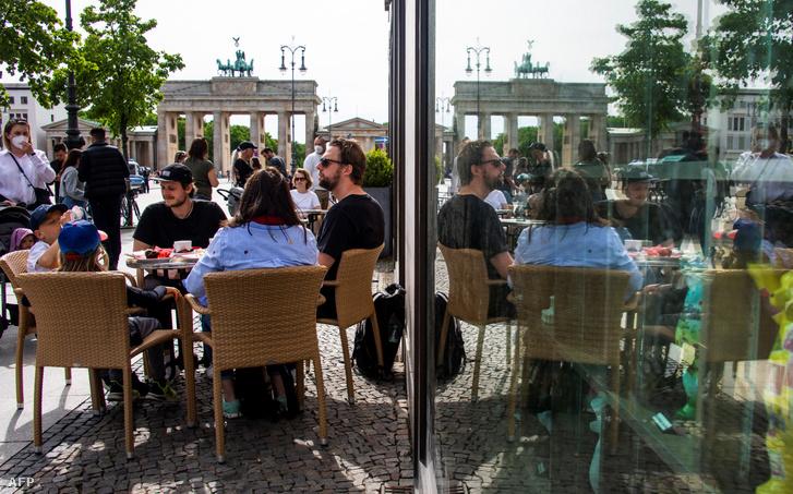Vendégek egy kávézó teraszán Berlinben 2021. május 24-én